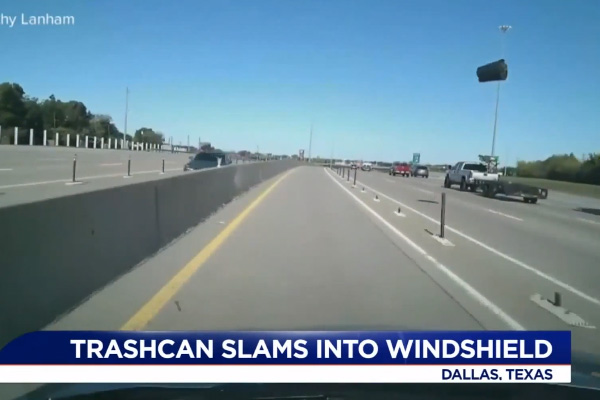 Driver survives scare with trash can crashing into windshield